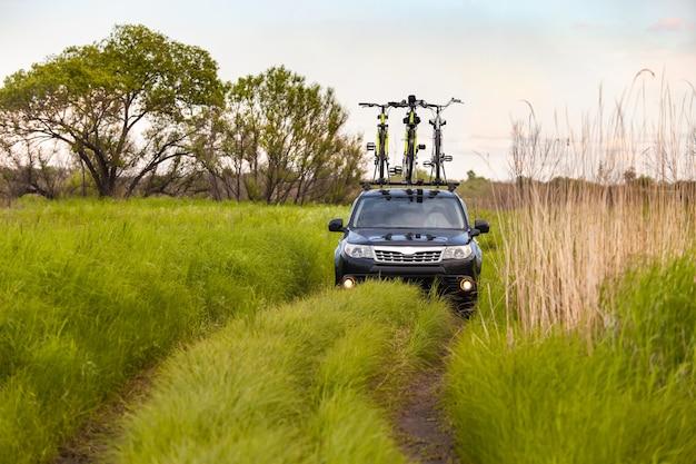 Crossover preto com três bicicletas no bagageiro em uma estrada de terra
