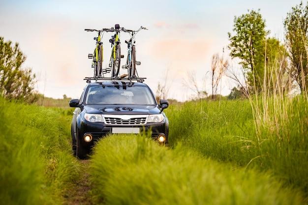 Crossover preto com três bicicletas no rack de teto em um prado