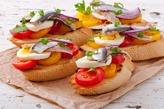 Crostini com anchovas, tomate e ovo, decorado com verduras