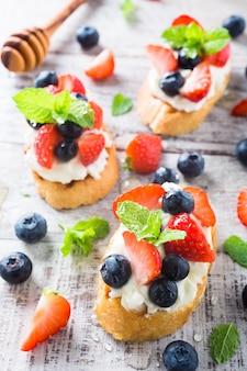 Crostini com baguete grelhado, cream cheese e frutas vermelhas