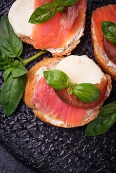 Crostini com salmão, mozarella, tomate e manjericão. entrada ou aperitivo italiano