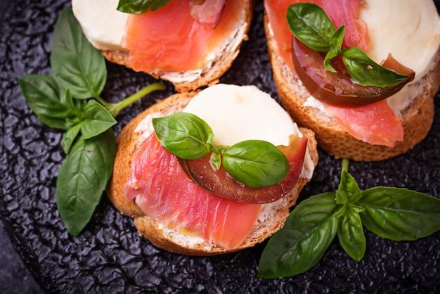 Crostini com salmão, mozarella, tomate e manjericão