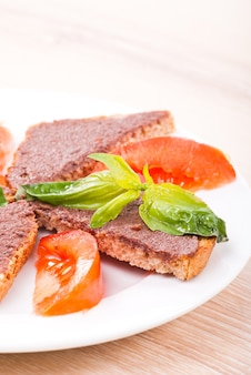 Crostinis com tapenade de azeitona, manjericão e tomate no prato