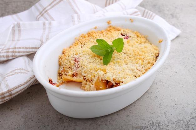 Crumble com morangos e maçãs em um prato branco e mesa de concreto.