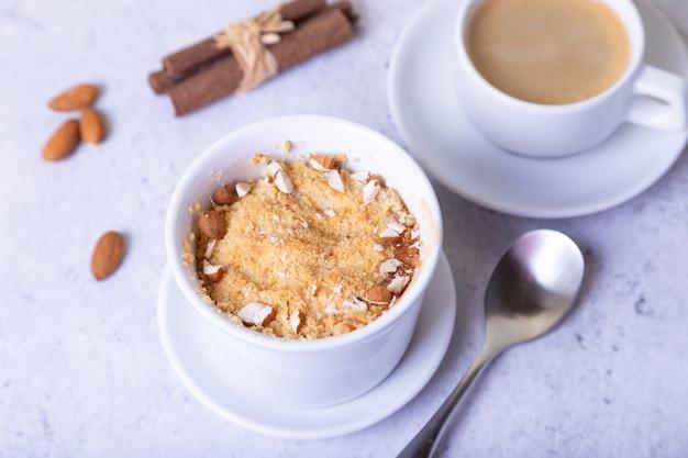 Crumble com pera caramelizada, canela e amêndoas em um ramekin branco. fechar-se.