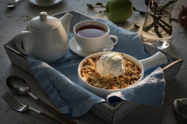 Crumble de maçã com uma bola de sorvete de baunilha e chá em uma bandeja de madeira. conceito de café da manhã