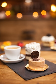 Crumbles de chocolate em uma saborosa sobremesa com biscoito por cima, sobre uma mesa de madeira perto de um delicioso café. mini bolo assado segundo receita tradicional.