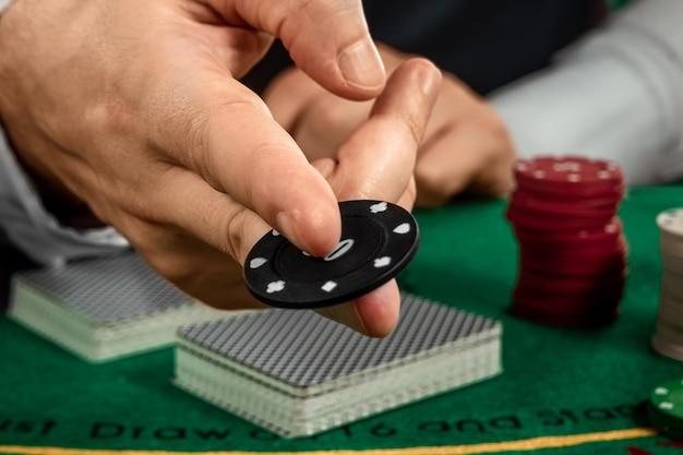 Crupiê de mãos masculinas em um cassino e jogando fichas em um pano verde closeup