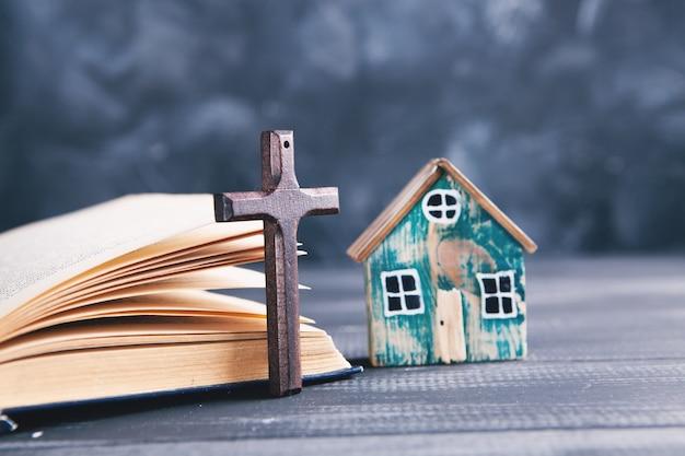 Cruz, casa e livro sobre a mesa