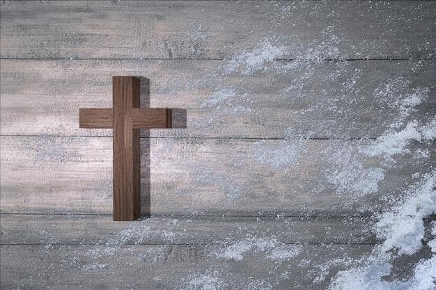 Cruz cristã com neve em fundo de madeira