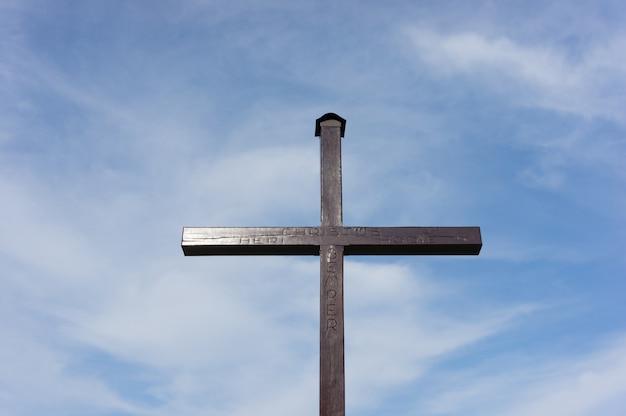 Cruz cristã feita de madeira sob um céu nublado