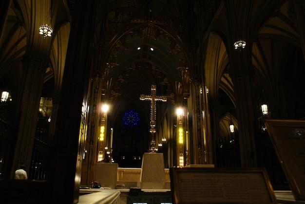 Cruz cristã iluminada com fundo preto dentro de uma igreja.