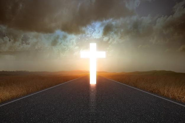 Cruz cristã no final da estrada com fundo de luz solar