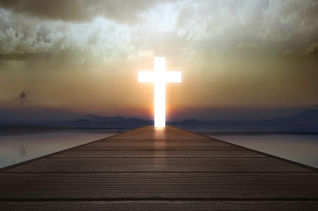 Cruz cristã no final do cais de madeira com fundo de luz solar