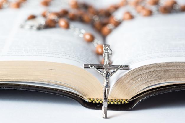 Cruz de contas de rosário descansando contra a bíblia