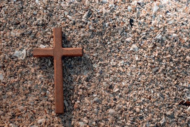Cruz de madeira com fundo de pedras.