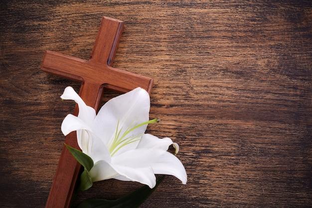 Cruz de madeira e lírio branco em mesa rústica