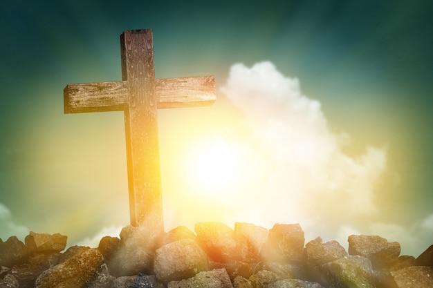 Cruz de madeira forma na colina rochosa ao pôr do sol com fundo azul do céu e nuvens, conceito de símbolo de religião