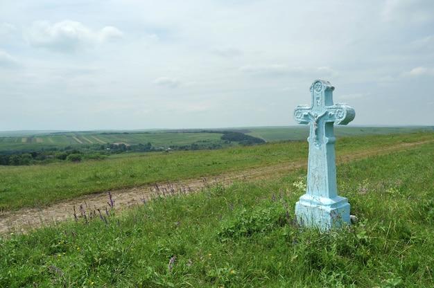 Cruz de pedra na estrada em um fundo de paisagem pitoresca.