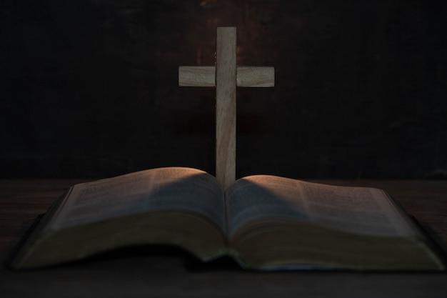 Cruz e bíblia sagrada na mesa de madeira
