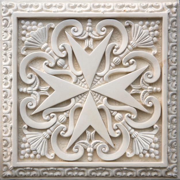 Cruz maltesa tradicional na fachada do edifício antigo em mdina, malta