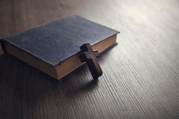 Cruz marrom na bíblia em uma madeira