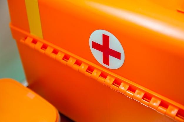 Cruz médica vermelha em uma mala laranja