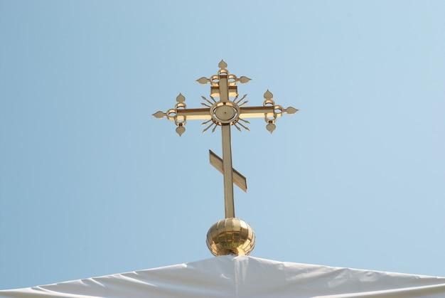 Cruz ortodoxa dourada com fundo de céu azul