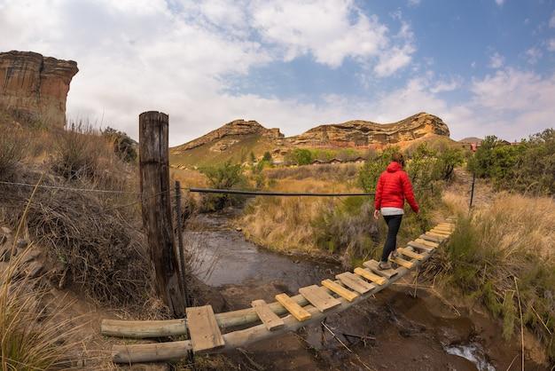 Cruzamento caminhante da mulher pendurado ponte pedonal suspensa em operação, no majestoso parque nacional golden gate highlands, áfrica do sul. conceito de aventura e pessoas viajando.