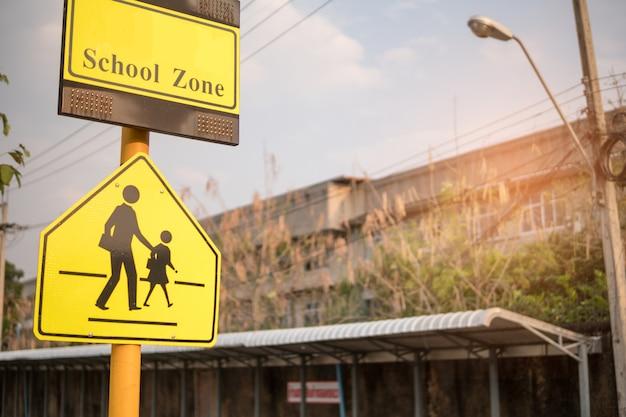 Cruzamento da escola do sinal do cuidado do sinal de estrada.