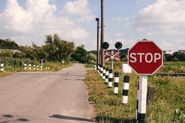 Cruzamento de ferrovia com um sinal de pare. trilhos de trem na paisagem do país. trilhos de trem na hora do pôr do sol. conceito de viagens locais.