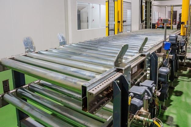 Cruzamento do transportador de rolos na fábrica de produção de alimentos