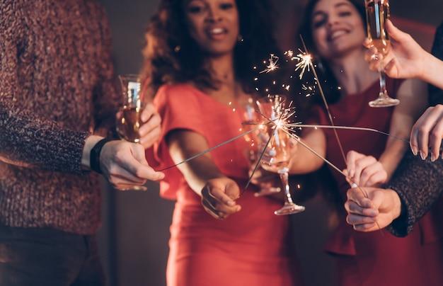 Cruzando varas. amigos multirraciais comemoram o ano novo e segurando luzes e copos de bengala com bebida