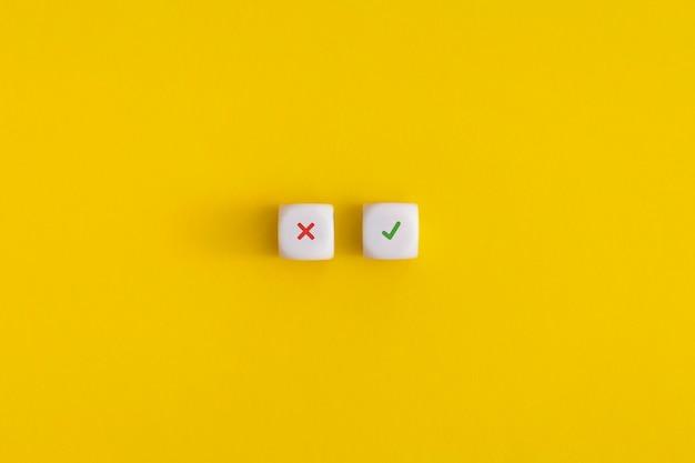 Cruze a marca de seleção em um cubos brancos sobre fundo amarelo. aprovação, votação ou conceito de decisão certa.