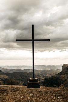 Cruze com vista panorâmica das montanhas sob um céu nublado e cinza