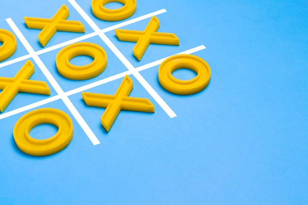 Cruzes de plástico amarelas e um dedo do pé e um campo regulamentado para jogar jogo da velha sobre um fundo azul. conceito xo vence o desafio. jogo educativo para crianças