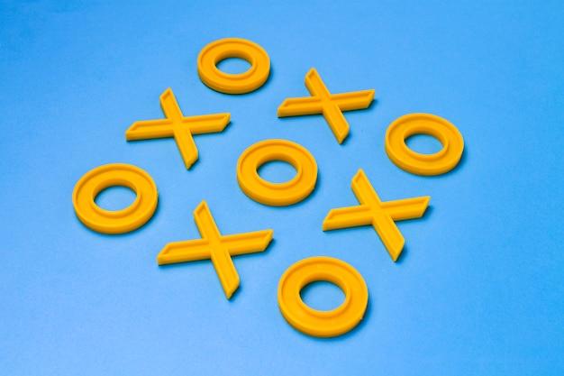 Cruzes de plástico amarelo e zeroches para jogar jogo da velha em uma superfície azul. conceito xo vence o desafio. jogo educativo para crianças