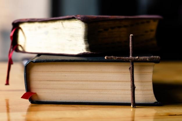 Cruzes e bíblia em uma mesa de madeira