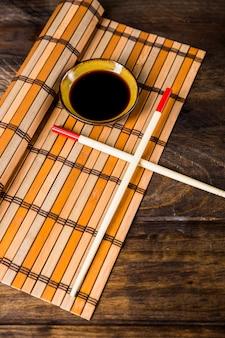 Cruzou os pauzinhos e tigela de molhos de soja na placemat sobre a mesa de madeira
