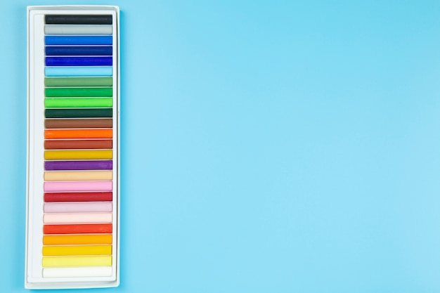 Cryaon no toplay pastel flatlay do copyspace do estilo do fundo azul.