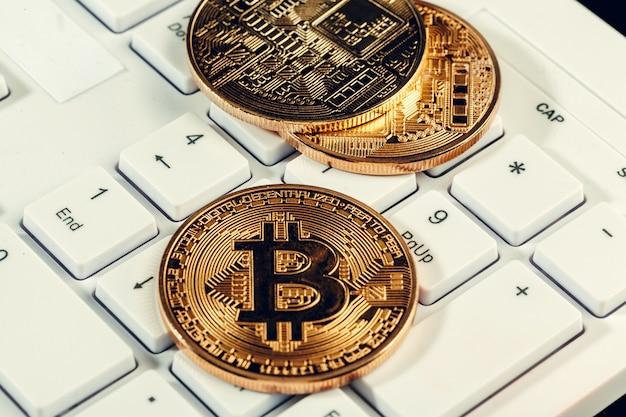 Cryptocurrency dourado da moeda do bitcoin no teclado do portátil.