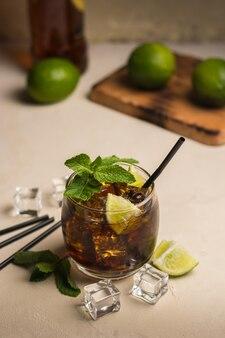 Cuba libre bebida com folhas de hortelã e pedaços de limão.
