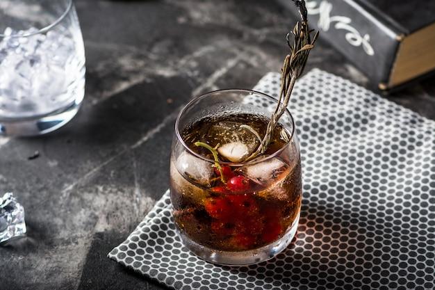 Cuba libre ou long island gelado de coquetel de chá com bebidas fortes, cola, limão e gelo em copo, longdrink frio ou limonada. cocktail com fogo. cocktail com fumaça.