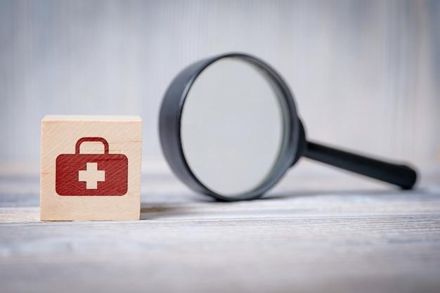 Cubo com ícone de bolsa médica e lupa. conceito de informações médicas de pesquisa, saúde.
