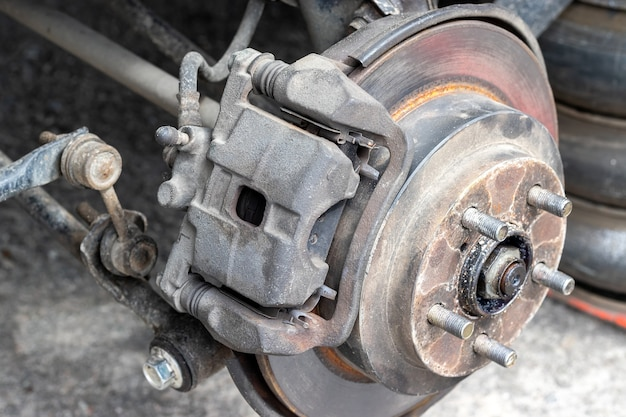 Cubo da roda traseira enferrujado com disco de freio no carro da oficina de pneus sem roda