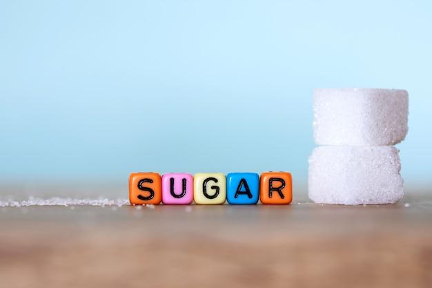 Cubo de açúcar branco e um bloco de alfabeto colorido de palavra de açúcar na mesa de madeira