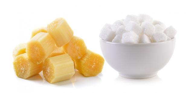 Cubo de açúcar na tigela e cana-de-açúcar isolado