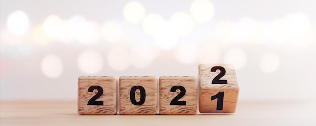 Cubo de bloco de madeira lançando entre 2021 e 2022 com bokeh de fundo para mudança e preparação de feliz natal e feliz ano novo por renderização em 3d.