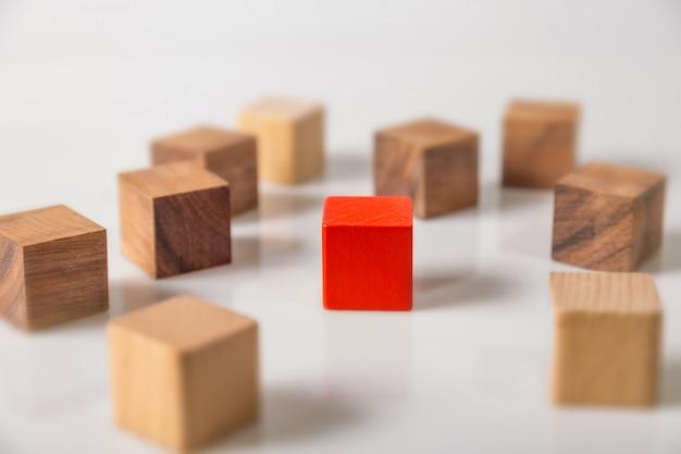 Cubo de formas geométricas de madeira vermelho e marrom, isolado no branco