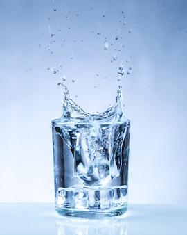 Cubo de gelo caindo em um copo d'água